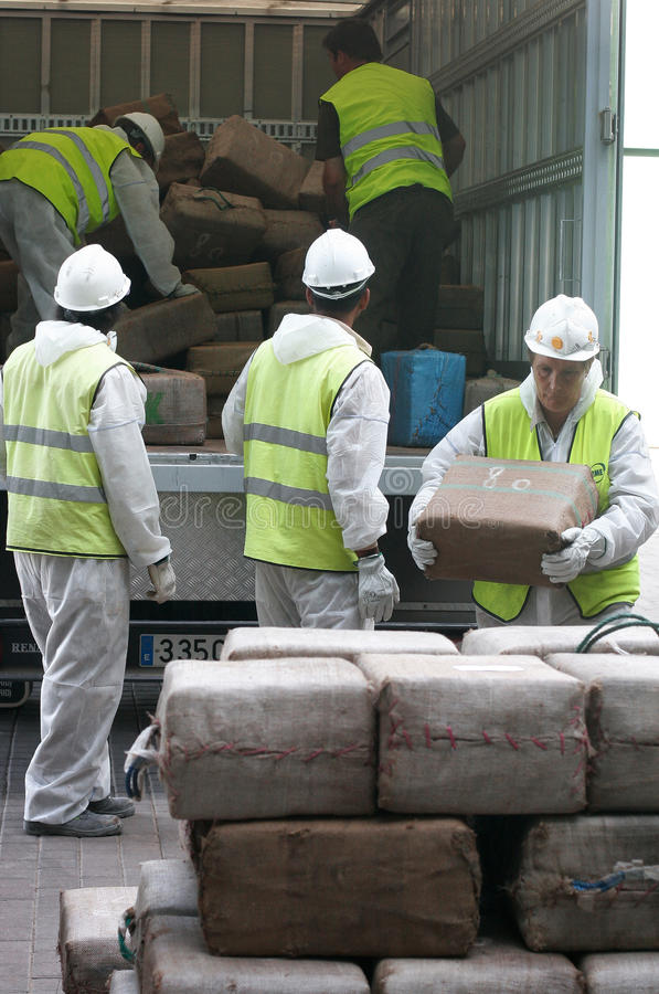 Workers retrieve drug packs from a truck before its destruction. Police workers retrieve packs of drugs from a truck to proceed to its incineration after the royalty free stock photography
