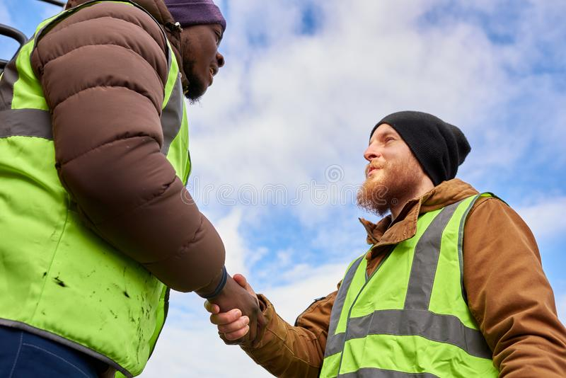 Workers Shaking Hands Outdoors royalty free stock photography