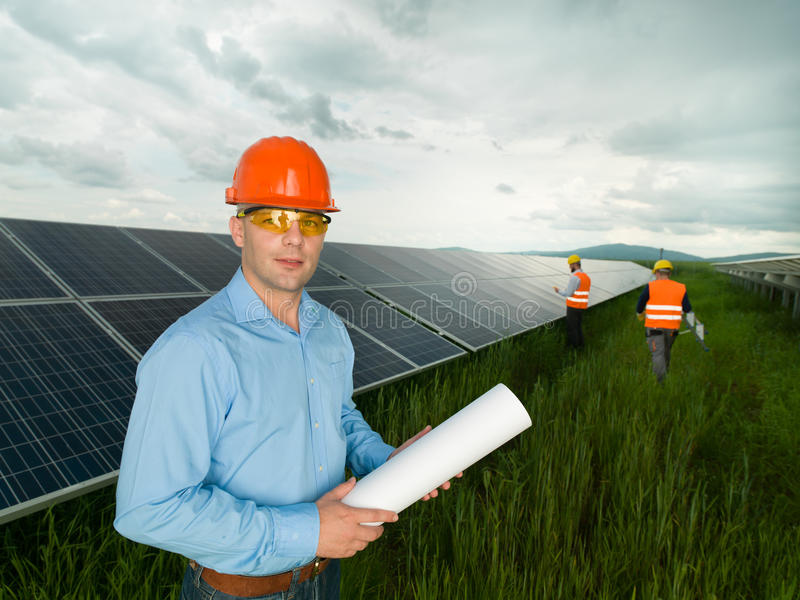 Workers in solar panel station. Male engineer wearing protection equipment, standing in solar panel station, holding blueprints, with two other workers in royalty free stock photography