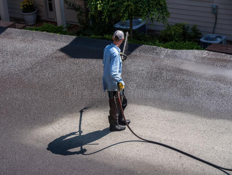 Workers spraying blacktop or asphalt sealer onto roadway. Workers applying blacktop sealer to asphalt street using a spray to provide a protective coat against royalty free stock images