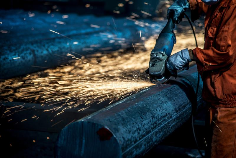 The workers in the steel mill are burnishing the steel. Sparks fly stock photo
