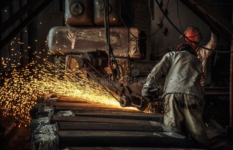 The workers in the steel mill are burnishing the steel. Sparks fly stock photography