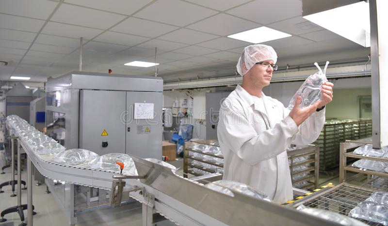 Workers in sterile protective clothing for quality control of in royalty free stock image