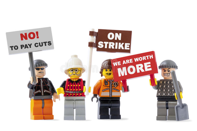Workers on strike concept. Vilnius, Lithuania - July 12, 2015: Workers on strike concept with four Lego toy figurines isolated on white background and holding stock images
