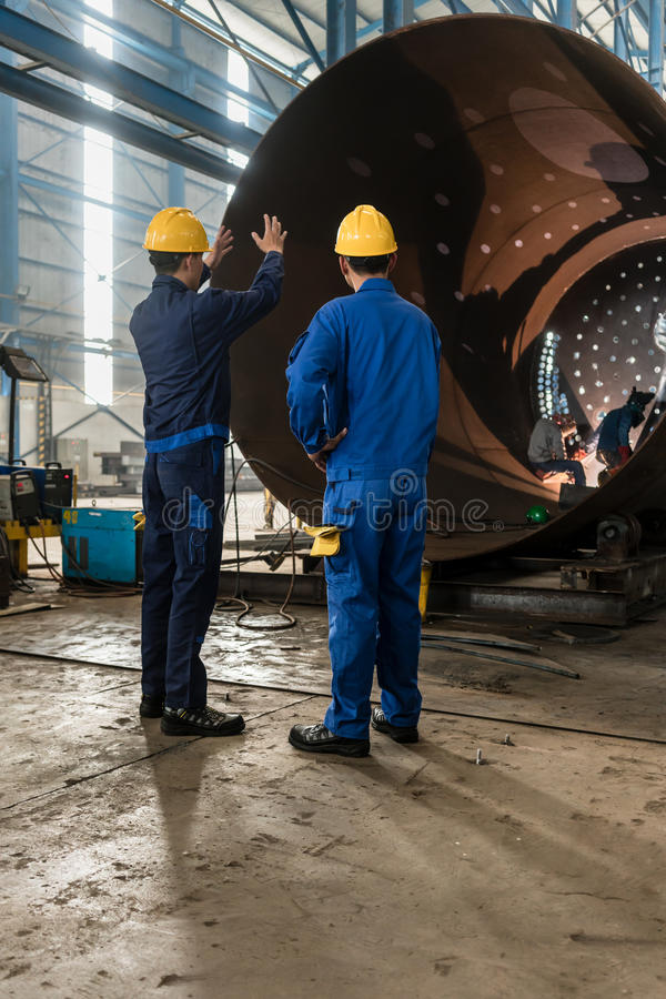 Workers supervising the manufacture of a metallic cylinder royalty free stock image