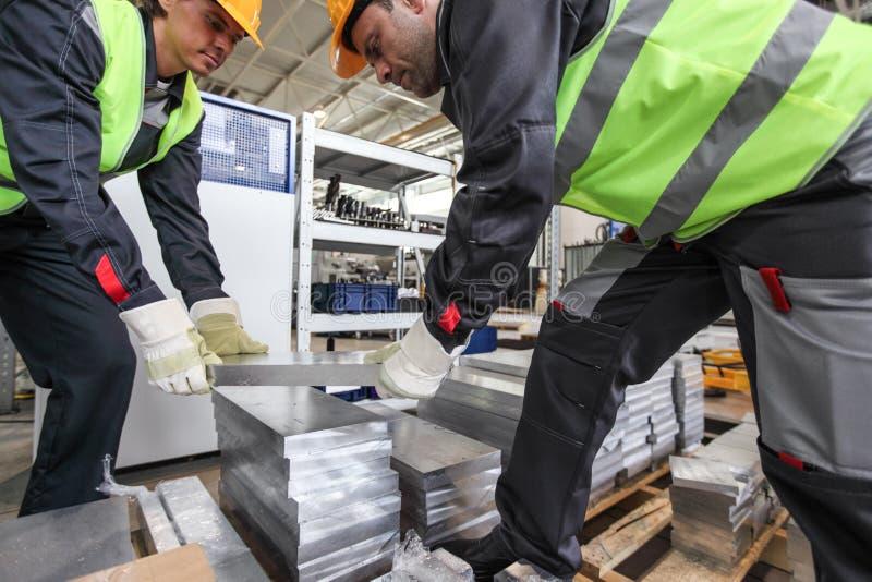 Workers taking aluminium billet. At CNC machine shop stock photos