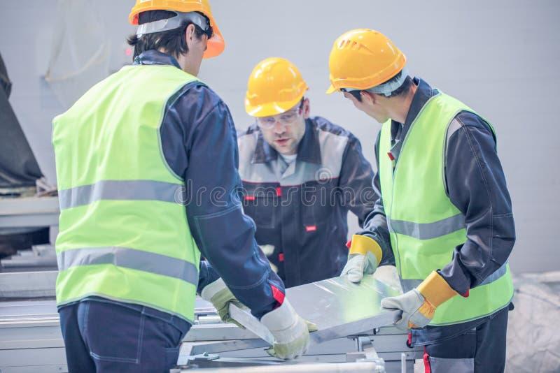 Workers taking aluminium billet stock image