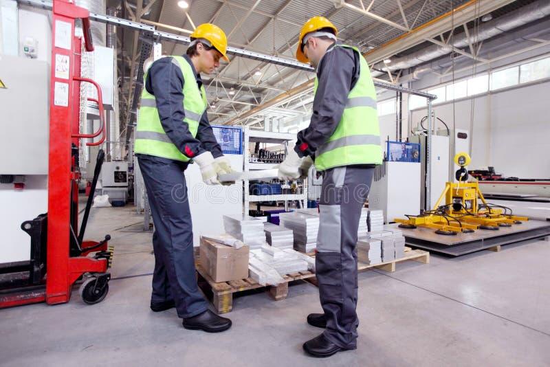 Workers taking aluminium billet. At CNC machine shop royalty free stock image