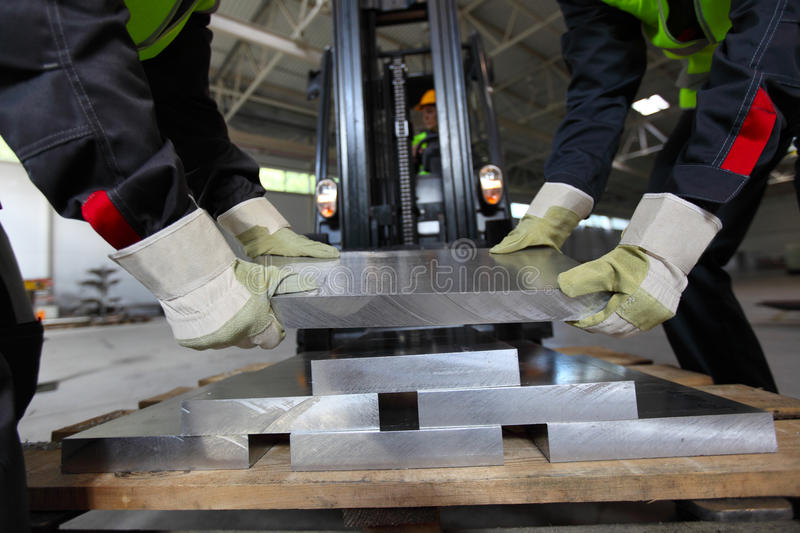 Workers taking aluminium billet. At CNC machine shop royalty free stock images