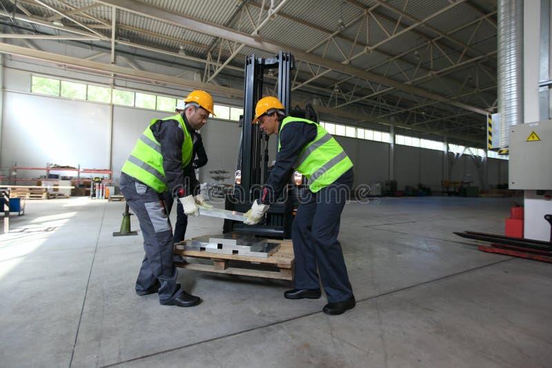 Workers taking aluminium billet. At CNC machine shop stock photo