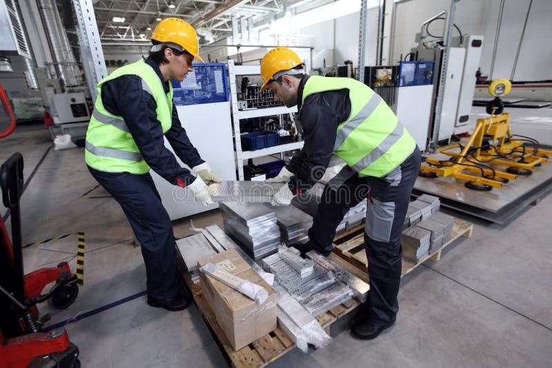 Workers taking aluminium billet. At CNC machine shop stock images