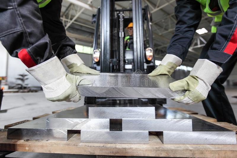 Workers taking aluminium billet. At CNC machine shop royalty free stock photography