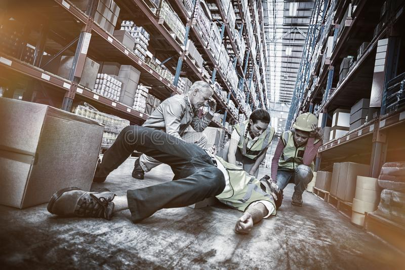 Workers taking care about their colleague lying on floor. In warehouse royalty free stock photos