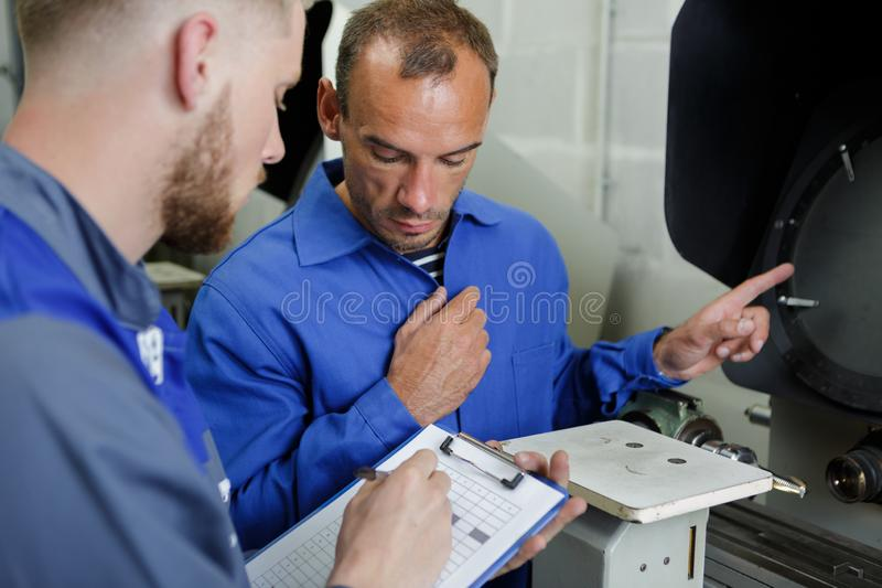 Workers taking machine readings in control room. Men stock photo