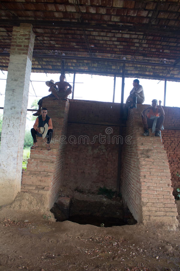 Workers taking a rest. Some workers are taking a rest in Cuba while they are waiting for the heavy shower to stop. They wait under a building royalty free stock photo