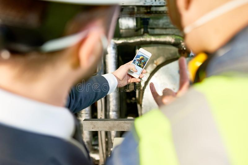 Workers Taking Selfie at Plant. High angle portrait of two factory workers taking selfie photo in workshop of modern plant, focus on image at smartphone screen stock image