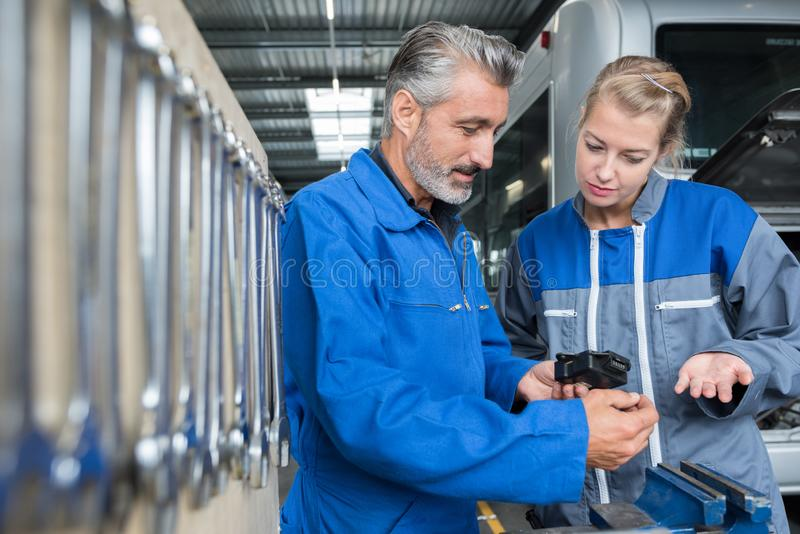 Workers with tools in workshop. Woman royalty free stock photo
