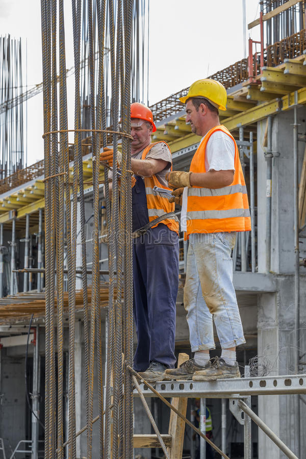 Workers tying reinforcing steel bars. BELGRADE, SERBIA - SEPTEMBER 08, 2016: Workers tying reinforcing steel bars with plier and wire on construction pillars stock photos