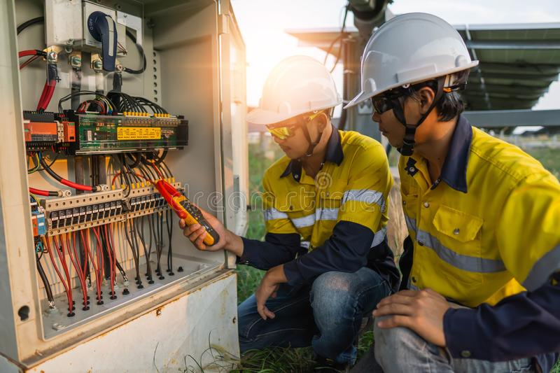 Workers use clamp meter to measure the current of electrical wires produced from solar energy for confirm to normal current.  royalty free stock images