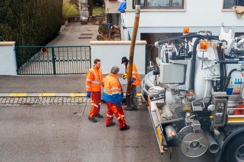 workers using sewerage truck and large pipe working on the clogged street rain water royalty free stock photography