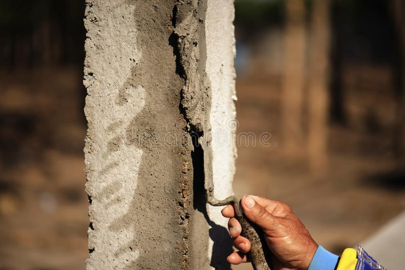 Workers are using a trowel to decorate the cement pillars into a beautiful ridge.  stock photography