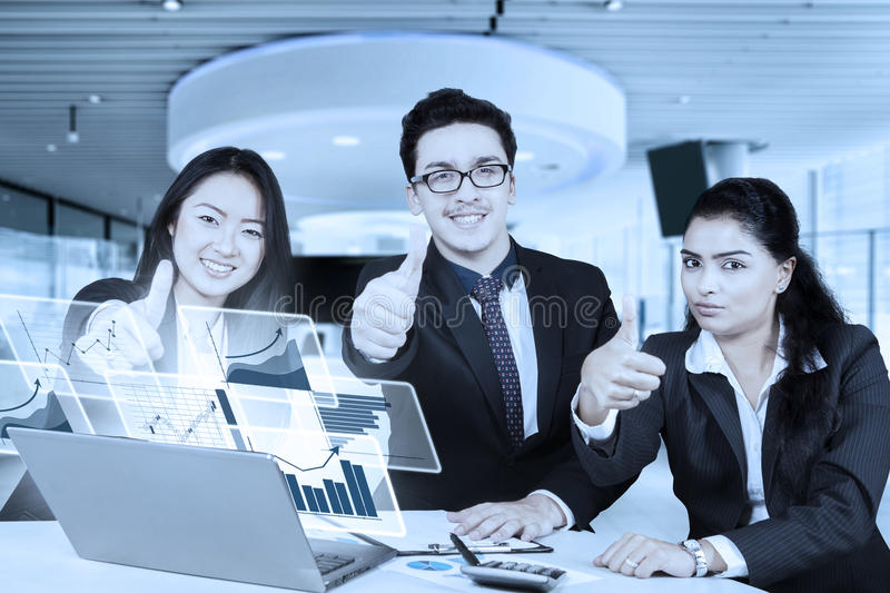 Workers with virtual chart and OK sign. Group of young business people showing thumbs up with virtual financial graph on the laptop stock photo