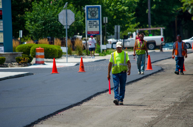 Working on a new road. Workers walk on part of a new road that is being paved with fresh hot asphalt stock image