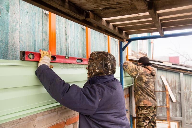 Workers walling the house with wall siding.  royalty free stock image