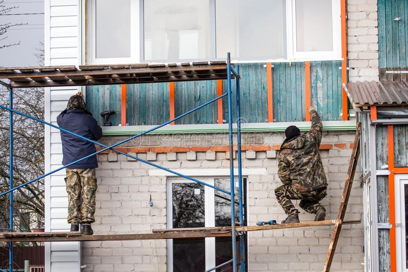 Workers walling the house with wall siding.  royalty free stock photos