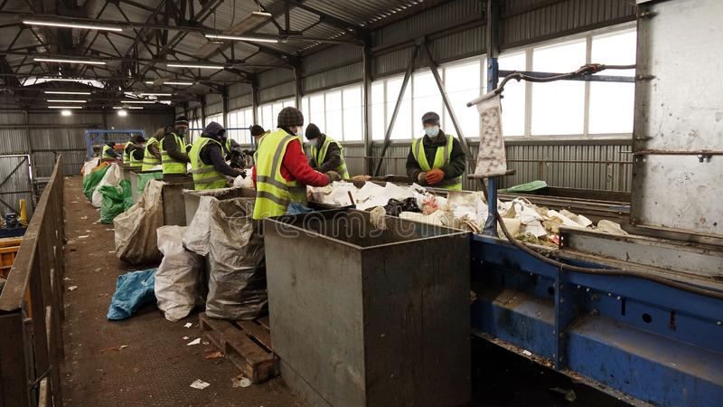 Workers at the waste processing plant. Sorting trash on a conveyor belt royalty free stock photos