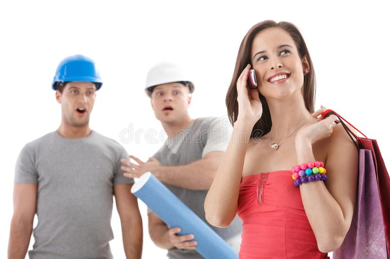 Workers watching attractive woman stock photos