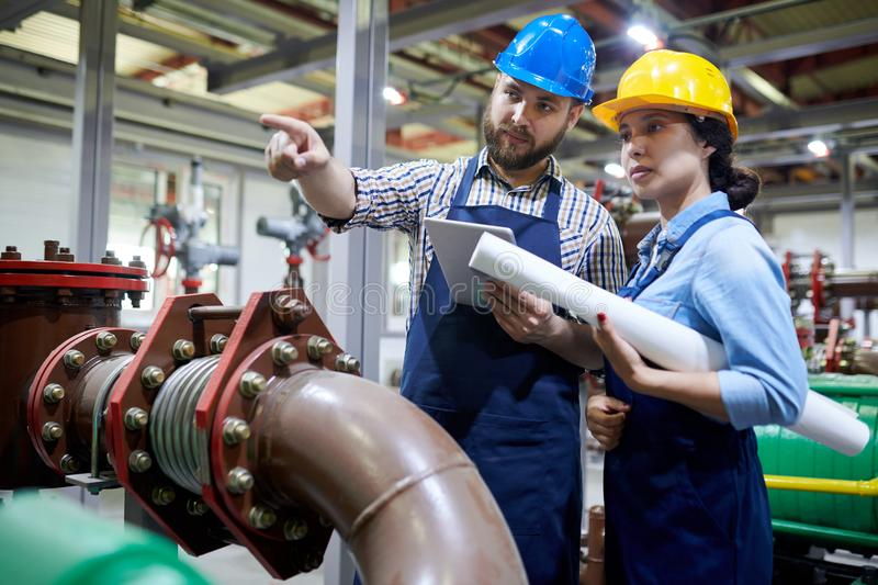 Workers in Water Purification System. Portrait of two factory workers pointing away while working with piping and machines in modern workshop, copy space royalty free stock image