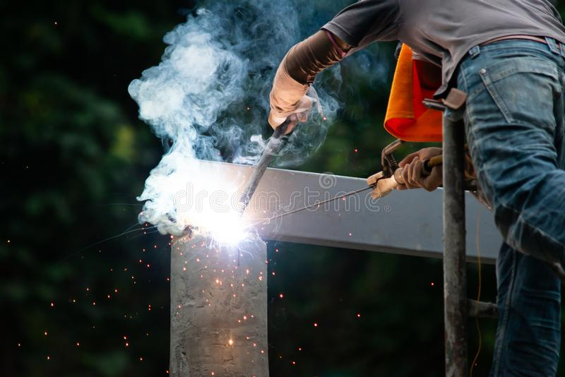 Workers are welding steel roof structure.  royalty free stock photography
