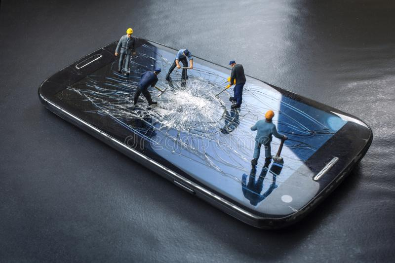 Workers work on the broken screen of a mobile phone. On a black background stock images