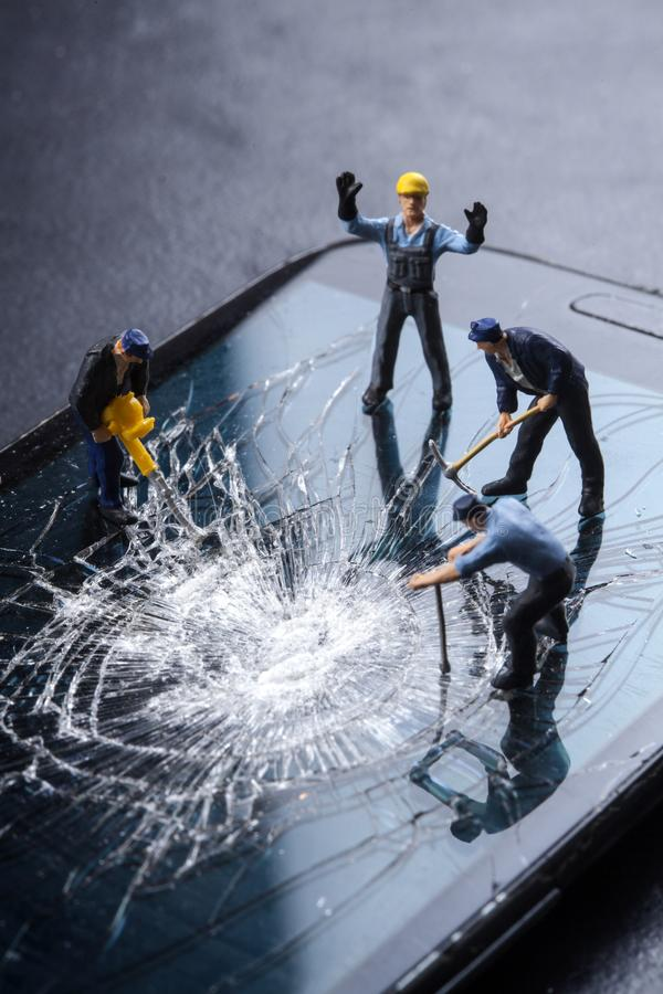 Workers work on the broken screen of a mobile phone. On a black background stock photos