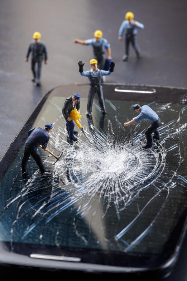 Workers work on the broken screen of a mobile phone. On a black background stock photography
