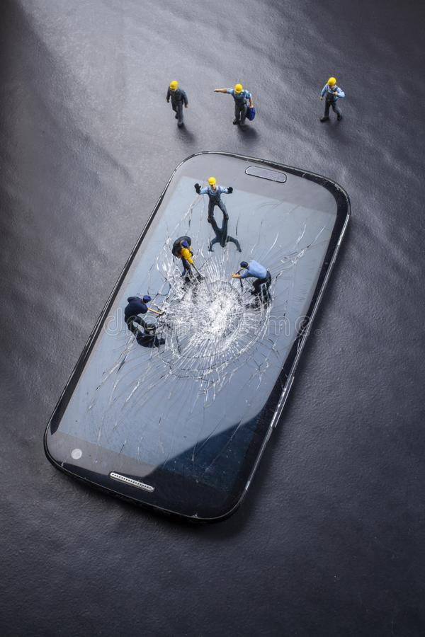 Workers work on the broken screen of a mobile phone. On a black background royalty free stock photography
