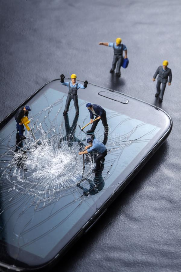 Workers work on the broken screen of a mobile phone. On a black background stock photo