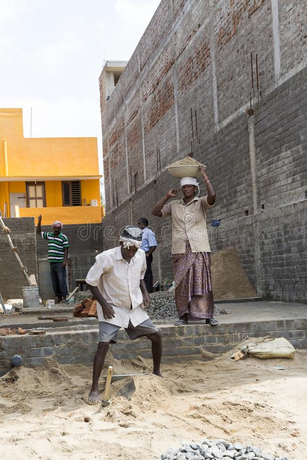 Workers work at the construction site. Work is under way to lay a wall of red brick. royalty free stock photos