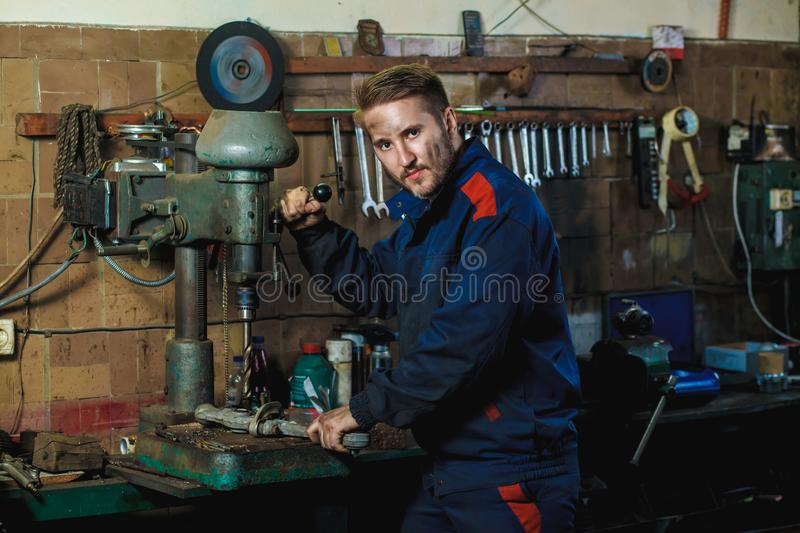 Workflow mechanic in a car garage. Auto service concept. A mechanic drills a detail on a drill press. Workflow mechanic in a car garage. Auto service concept royalty free stock photography