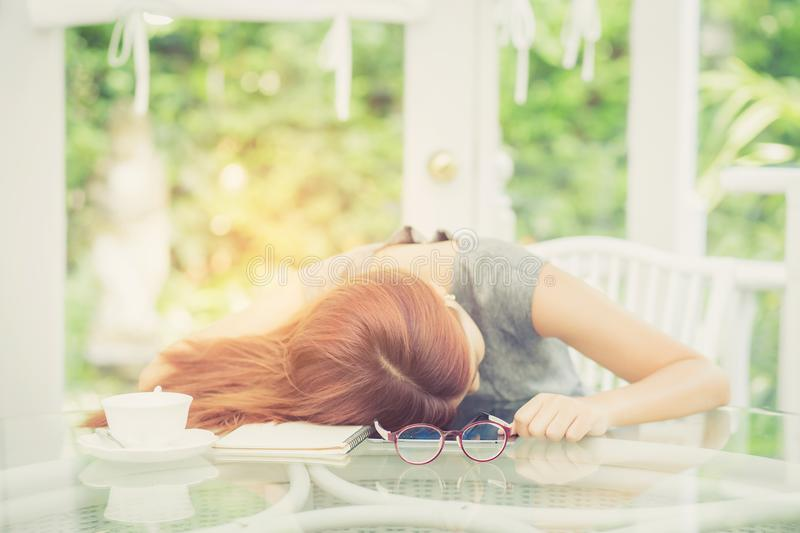 Workhard young asian woman tried and sleep on desk in the garden royalty free stock photo