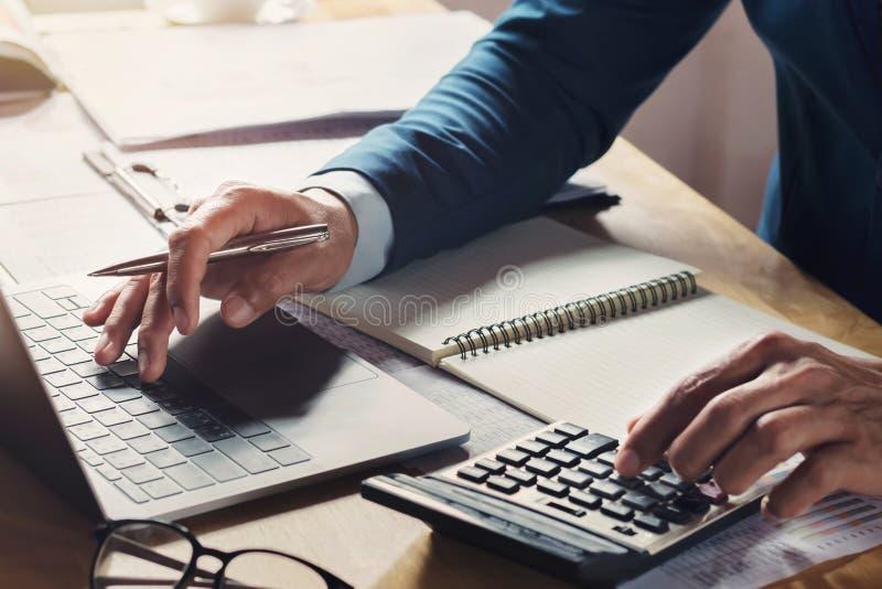 workig d'homme d'affaires et calculatrice d'utilisation avec l'ordinateur portable photos libres de droits