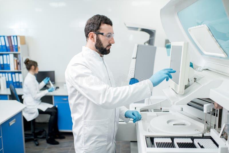 Workign de los ayudantes de laboratorio con el analizer foto de archivo