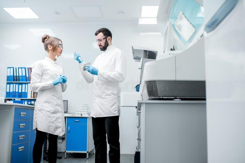 Workign de los ayudantes de laboratorio con los tubos de ensayo fotos de archivo