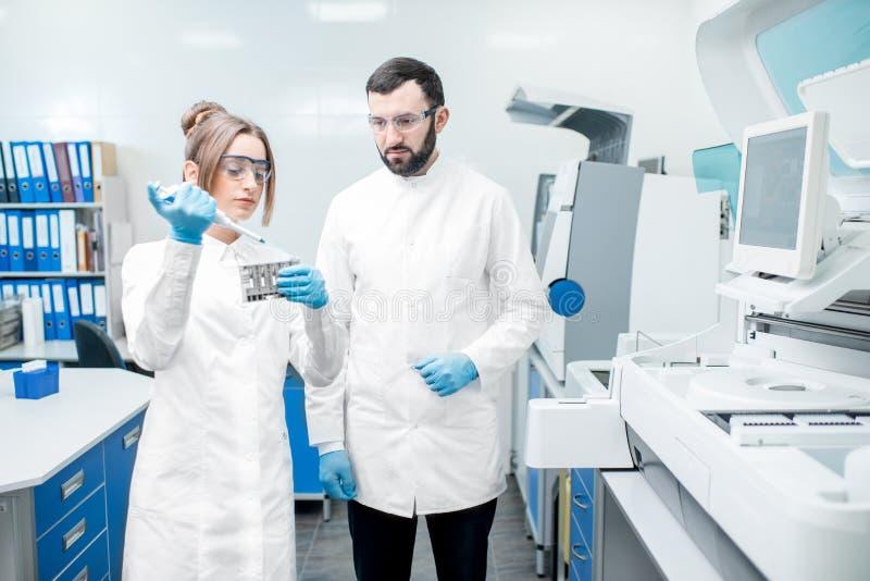 Workign de los ayudantes de laboratorio con los tubos de ensayo fotografía de archivo