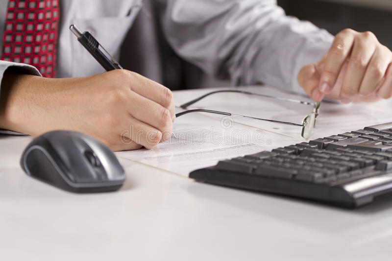Working. A male model wearing shirt and red tie working at his office royalty free stock photo