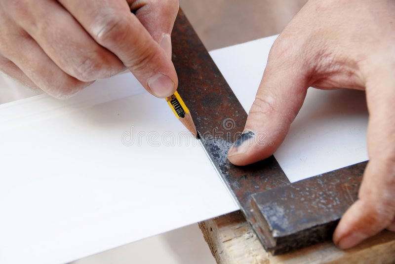 Working. Manual worker hands drawing a line on white plastic track stock image