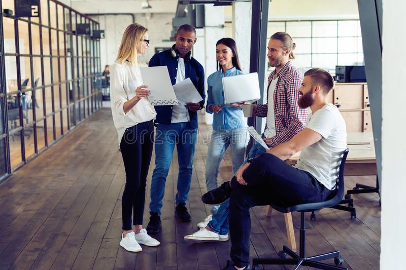 Working as a team. Full length of young modern people in smart casual wear planning business strategy while young woman. Working as a team. Full length of young royalty free stock images