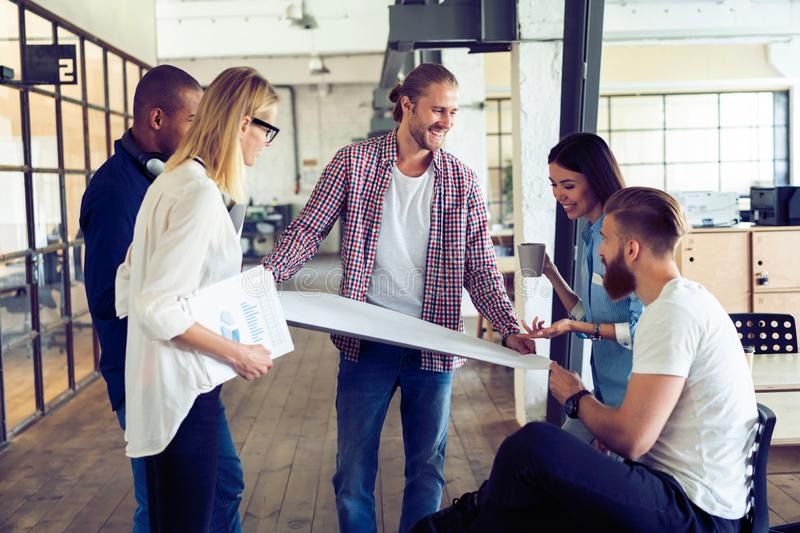 Working as a team. Full length of young modern people in smart casual wear planning business strategy while young woman. Working as a team. Full length of young royalty free stock image