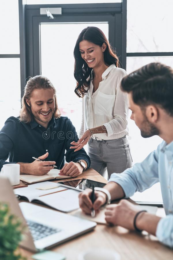 Working as team. Young modern colleagues in smart casual wear working together and smiling while spending time in the office stock photos